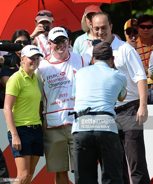 Stacy Lewis of the US poses with Travis Wilson her best caddy of the year 2013 during round three of the HSBC Women's Champions LPGA golf tournament...