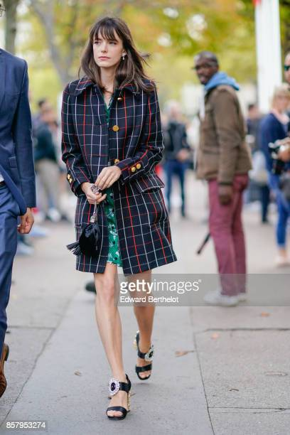 Stacy Martin wears a checkered coat a green dress outside Miu Miu during Paris Fashion Week Womenswear Spring/Summer 2018 on October 3 2017 in Paris...