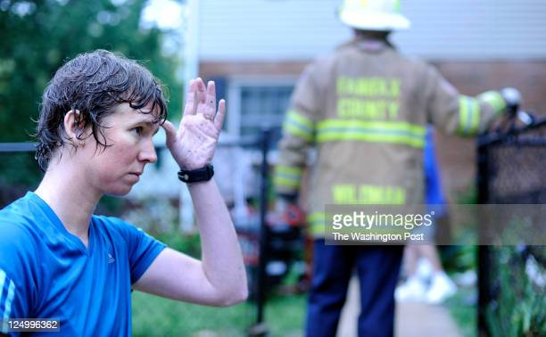Stacy Rodgers of Fenwick Drive watches an electric generator brought into her home by Fairfax Fire Fighters to power a sump pump in order to remove...