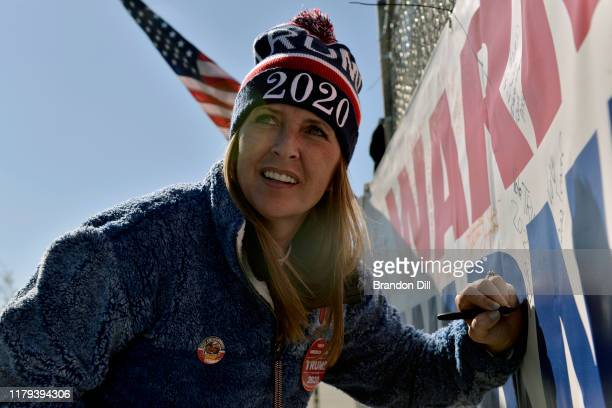 Stacy Williams signs a banner before President Donald Trump's Keep America Great campaign rally at BancorpSouth Arena on November 1 2019 in Tupelo...