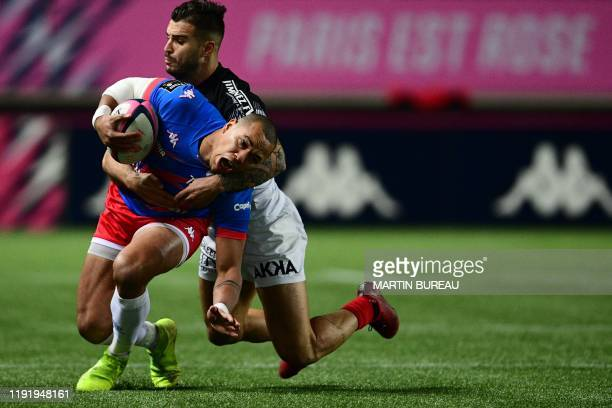 Stade Français French centre Gael Fickou is tackled by Toulouses French centre Sofiane Guitoune during the Top 14 rugby union match between Stade...