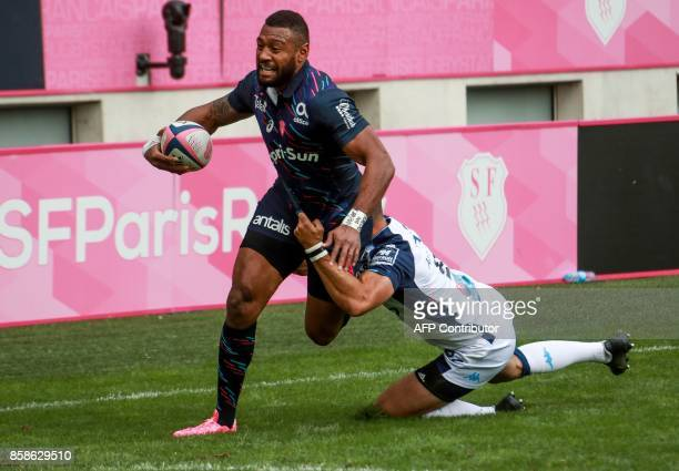 Stade Francais centre Waisea Vuidravuwalu is tackled by Montpellier 's number 8 Ruan Pienaar during the Top14 rugby union match between Stade...