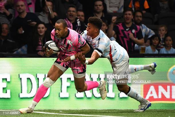 Stade Francais' French center Gael Fickou vies with Racing92's Fiji flyhalf Ben Volavola before scoring a try during the French Top 14 rugby union...