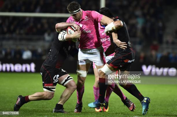 Stade Francais' French lock Alexandre Flanquart vies with Lyon's Australian flanker Liam Gill and Lyon's Australian center Rudi Wulf during the...