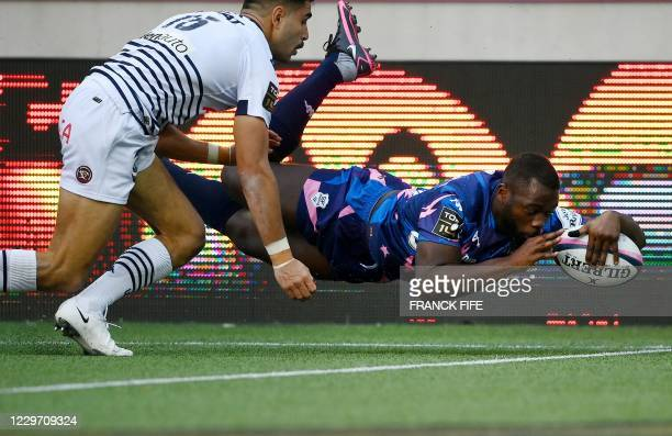 Stade Francais' French wing Lester Etien scores a try in front of Bordeaux-Begles' French full-back Romain Buros during the French Top 14 rugby union...