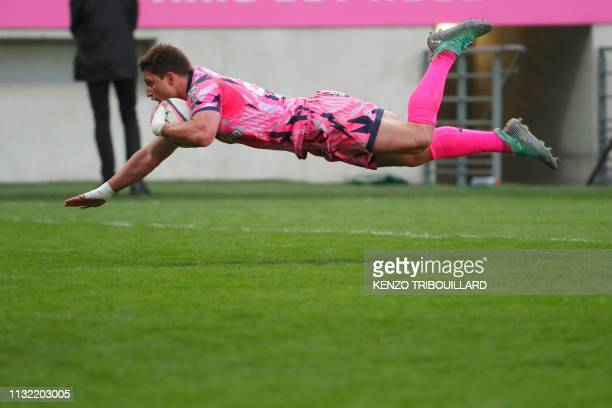 Stade Francais' South-African scrum-half Piet Van Zyl jumps to score a try during the French Top 14 rugby union match between Stade Francais and...