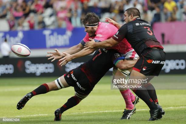 Stade Francais's French lock Paul Gabrillagues passes the ball as he is tackled by Lyon's Australian flanker Liam Gill and Lyon's Argentinian prop...