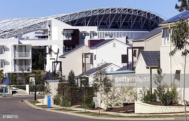 Stadium Australia stands behind the Athletes' Village complex as it was unveiled 09 August 2000 at Homebush Bay in Sydney. The village, which...