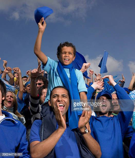 Stadium crowd cheering, boy (5-7) on father's shoulders, waving cap