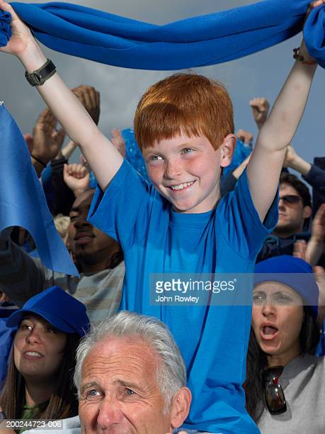 Stadium crowd cheering, boy (7-9) sitting grandfather's shoulders