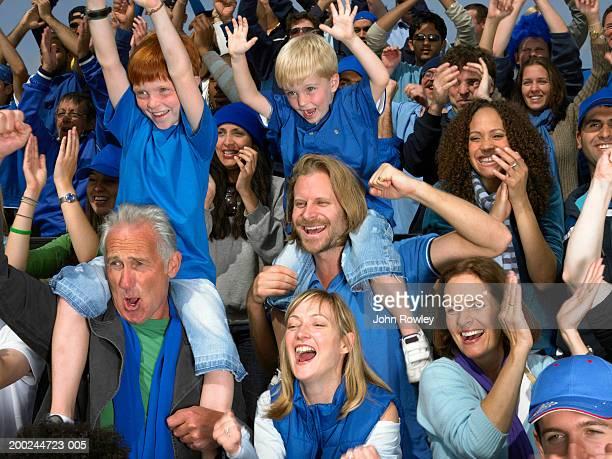 Stadium crowd cheering, boys (5-9) sitting on men's shoulders, waving