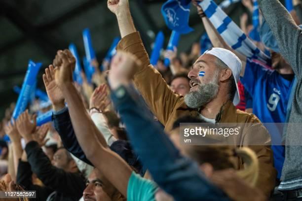 stadion menge jubeln mit erhobenen armen - fan stock-fotos und bilder
