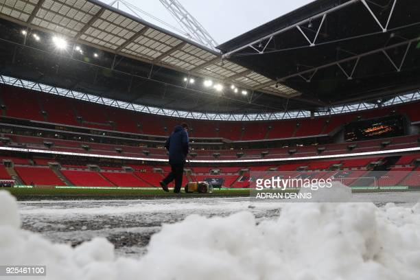 A stadium employee uses a snow blower on the field before the English FA Cup 5th round replay football match between Tottenham Hotspur and Rochdale...