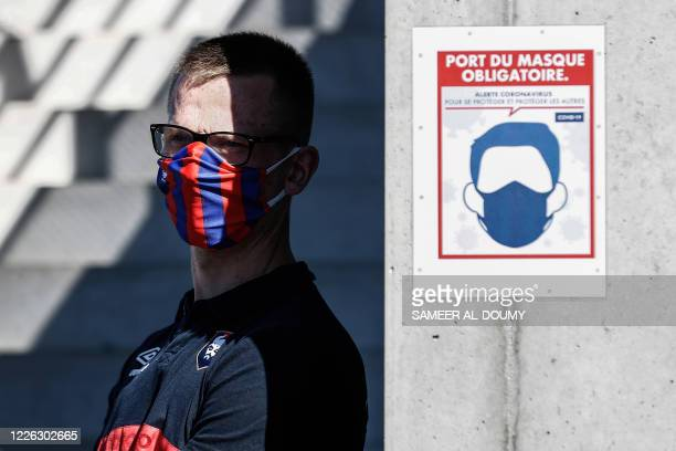 Stadium employee wearing a protective face mask stands past a sign reminding to spectators and staff to wear a mask during the French L2 friendly...