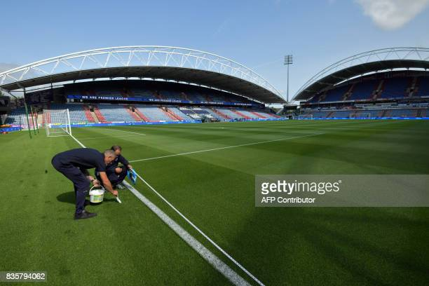 Stadium employees freshen the pitch prior to the English Premier League football match between Huddersfield Town and Newcastle United at the John...