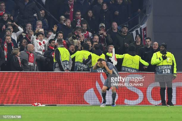 Stadium employees try to prevent Ajax's supporters to throw projectiles at Bayern Munich's Brazilian defender Rafinha during the UEFA Champions...