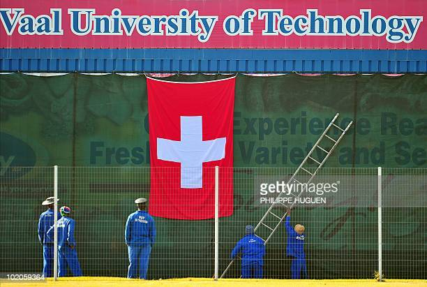 Stadium gardeners hang a Swiss flag before training by Switzerland's football team on June 14 2010 at the Vaal University Technology in...