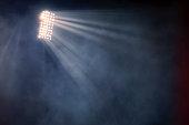 stadium lights and smoke against dark night sky background