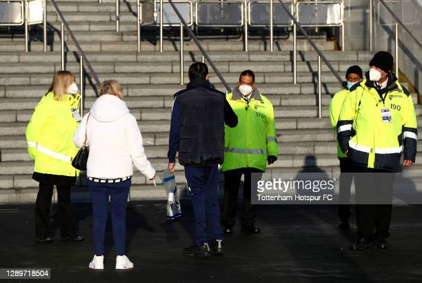 Stadium security wearing protective masks are seen speaking to fans outside the stadium ahead of the Premier League match between Tottenham Hotspur...