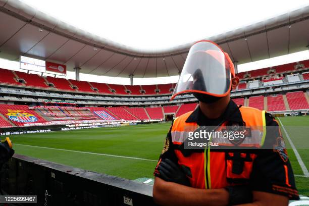 Stadium staff stands guard wearing a face mask and a shield as part of the health protocol to halt the spread of COVID -19 during the match between...