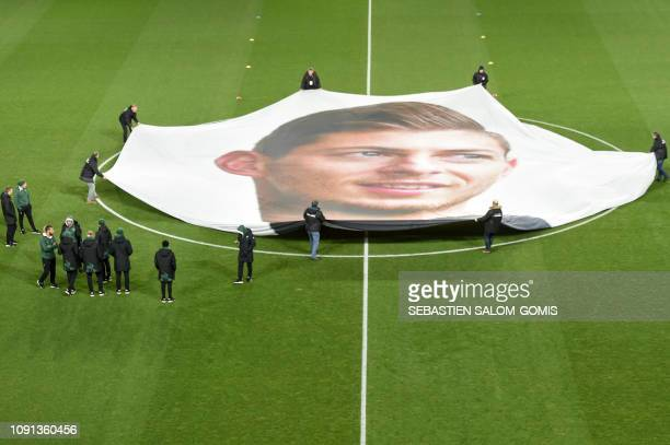 Stadium stewards display a portrait of Argentinian forward Emilianio Sala whose plane disappeared over the Channel Islands over a week prior in the...