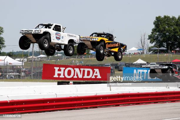 Stadium Super Trucks driver Bill Hynes is in front of Jerrett Brooks as their trucks go airborne on the front straightaway after launching off a ramp...