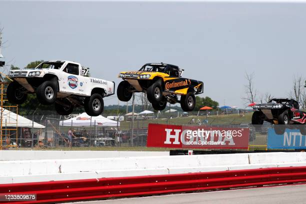 Stadium Super Trucks driver Bill Hynes is in front of Jerrett Brooks and Jack Noland as their trucks go airborne on the front straightaway after...