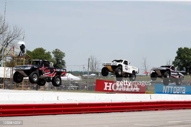 Stadium Super Trucks drivers Jeff Noland and Bill Hynes and Max Gordon race on the front straightaway and go airborne after launching off a ramp...