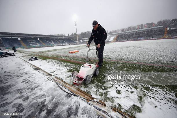 A stadium worker prepares the snow covered pitch prior to the Second Bundesliga match between SV Darmstadt 98 and SSV Jahn Regensburg at MerckStadion...