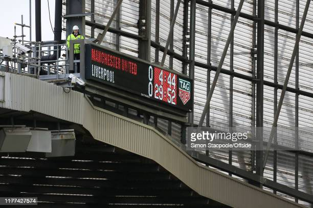 A stadium worker watches from a platform above the scoreboard during the Premier League match between Manchester United and Liverpool FC at Old...