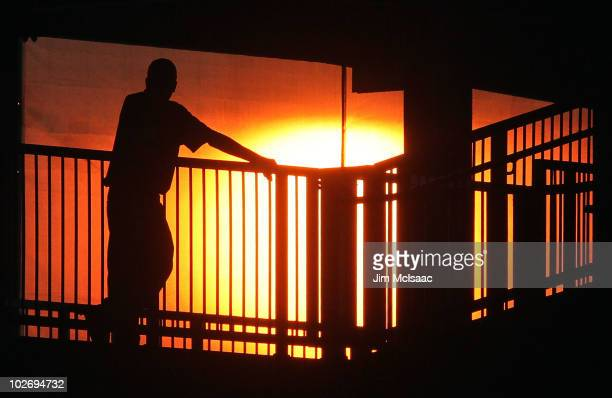 A stadium worker watches the sun set during the game between the New York Mets and the Cincinnati Reds on July 7 2010 at Citi Field in the Flushing...