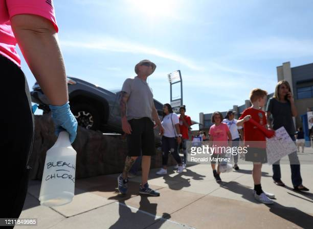 A stadium worker wears rubber gloves while carrying a bottle of bleach/chlorine as fans walk around Toyota Stadium before the 2020 SheBelieves Cup on...
