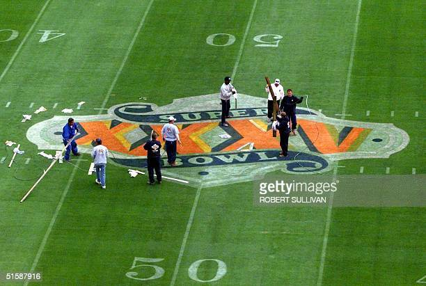 Stadium workers paint the Super Bowl XXXV logo on the field 22 January 2001 at Raymond James Stadium in Tampa FloridaThe New York Giants will face...