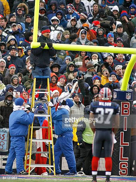 Stadium workers straigten the goalpost after it was blown over by high winds during play between the Buffalo Bills and the New England Patriots at...