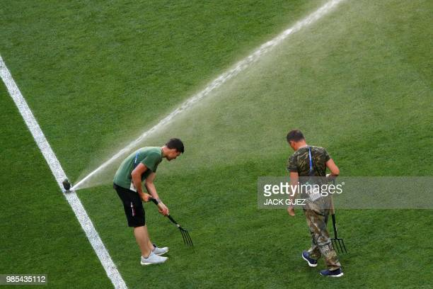 Stadium's gardeners take care of the lawn as they water it after a training session at the Mordovia Arena in Saransk on June 27 on the eve of the...