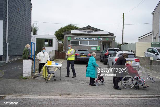 Staff and a volunteer wait for people to attend an NHS walk-up vaccination unit outside the village hall on September 25, 2021 in the village of...