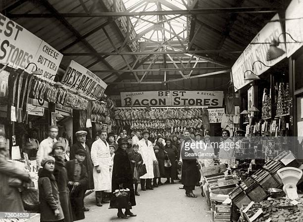Staff and customers at a covered market in East London circa 1920