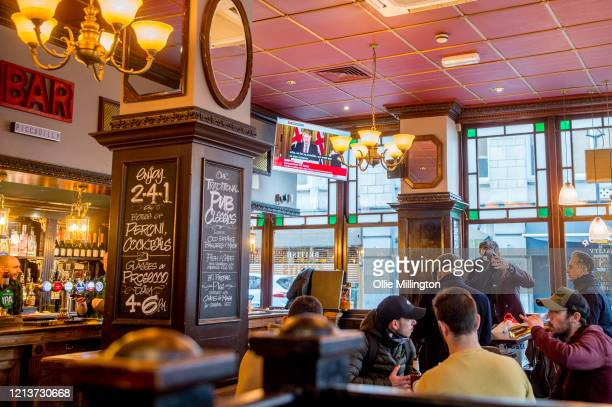 Staff and customers in a Soho London pub watch a live TV press conference by The British government on March 20, 2020 in London, England. British...