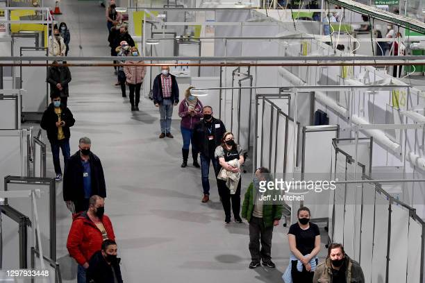 Staff and key workers queue in the Louisa Jordan Hospital before receiving the coronavirus vaccine on January 23, 2021 in Glasgow, Scotland. Five...