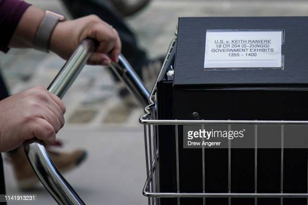 Staff and members of the prosecution team push carts full of court documents related to the US v Keith Raniere case as they arrive at the US District...
