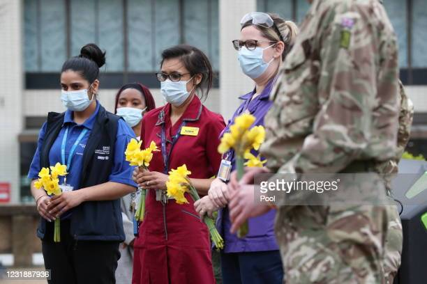 Staff and military personnel who have been assisting hold flowers to place near the statue of Crimean War nurse Mary Seacole during a ceremony to...
