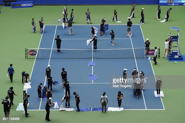 Staff are seen drying the court with towels during the quarter final match between Anastasia Pavlyuchenkova of Russia and Barbora Strycova of Czech...