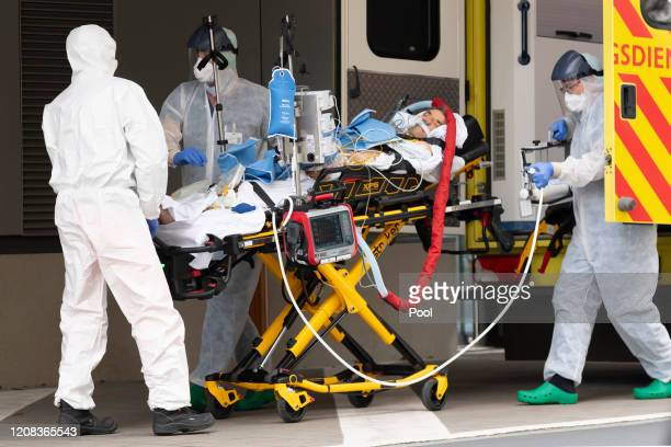 Staff are seen with a patient from Italy at the Corona Outpatient Clinic in the Dresden University Hospital on March 26, 2020 in Dresden, Germany....