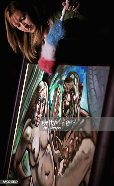 Staff at McTeers auctioneers dust the Peter Howson controversial Madonna and Guy painting on May 27 2009 in Glasgow Scotland The painting of the pop...