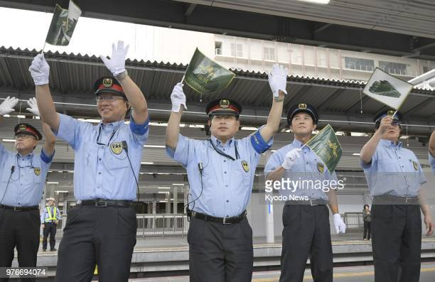 Staff at Osaka Station watch West Japan Railway Co's Twilight Express Mizukaze luxury sleeper train leave the station in the western Japan prefecture...