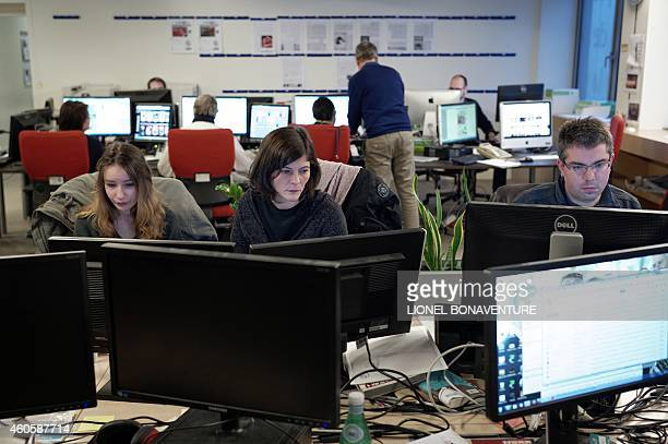 Staff at the French daily newspaper Le Monde headquarters work on December 17 2014 in Paris the close the day's edition on the eve of the...