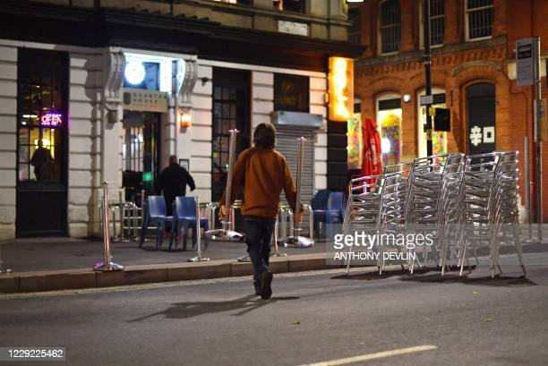 Staff at the Quarter House begin to clear away tables and chairs in Manchester city centre northwest England ahead of new coronavirus restrictions...