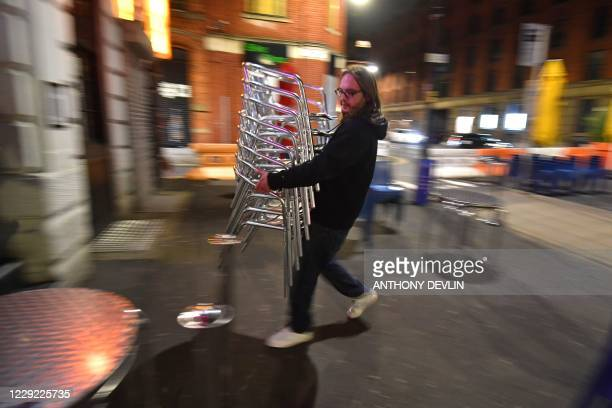 Staff at the Quarter House begin to clear away tables and chairs in Manchester northwest England ahead of new coronavirus restrictions coming into...