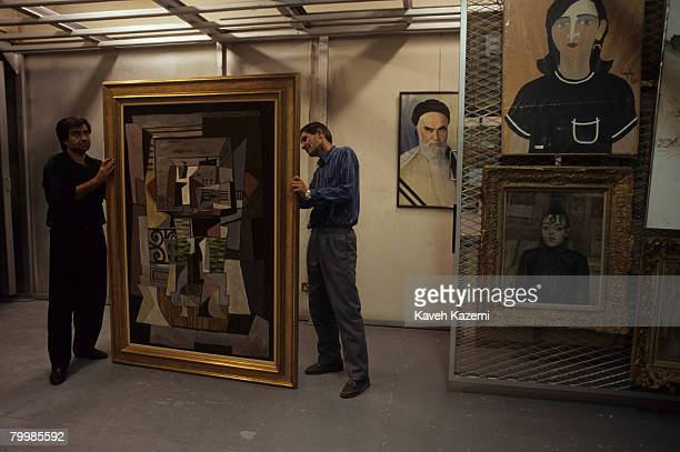 Staff at the Tehran Museum of Contemporary Art inspect Picasso's painting 'Open Window on the Rue de Penthievre in Paris', September 1993. At bottom...