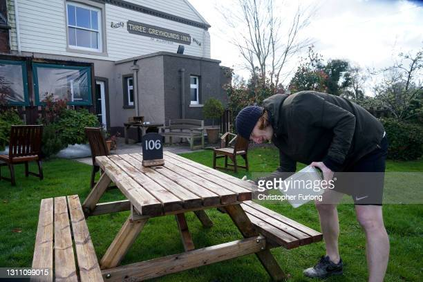 Staff at the Three Greyhounds Pub in the village of Allostock prepare outdoor tables ready for next week's opening on April 06, 2021 in Knutsford,...